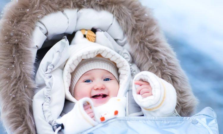 Baby i barnvagn på vintern i åkpåse