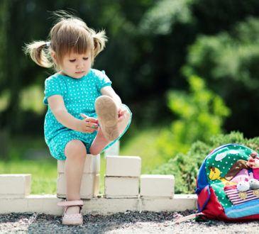 Flicka sätter på sig sandaler