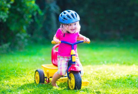 Flicka cyklar på sin trehjuling